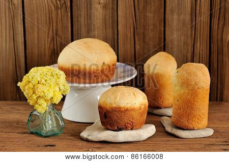 Paska, East European Easter Sweet Breads With Yellow Flowers On Wooden Background