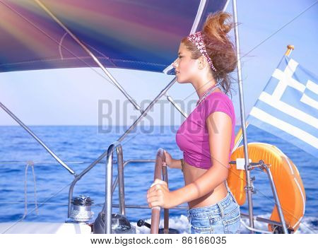 Side view of a  sexy girl behind the wheel of a yacht, young woman enjoying summer vacation on luxury sailboat, recreation travel and active lifestyle concept