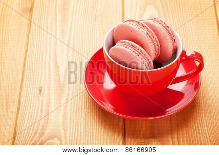 Pink macaron cookies in coffee cup on wooden table background