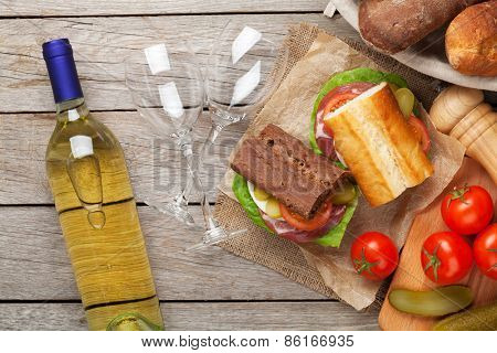 Sandwiches and white wine on wooden table. Top view
