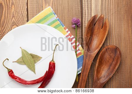 Wood kitchen utensils and spices over wooden table