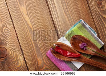 Wood kitchen utensils and spices over wooden table background with copy space