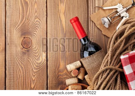 Red wine bottle, corks and corkscrew over wooden table background. Top view with copy space