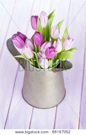 Watering can with purple tulips on wooden table