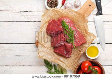 Raw fillet beef steak and spices on wooden table. Top view with copy space