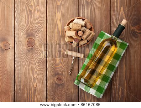 White wine bottle, corks and corkscrew over wooden table background. Top view with copy space
