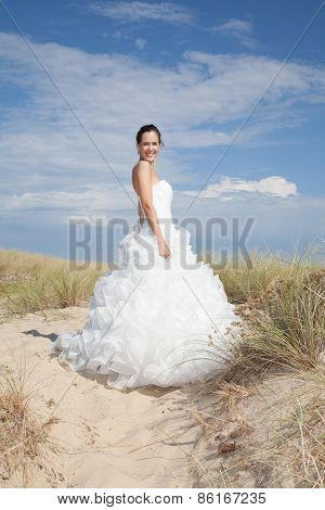Bride In Wedding Dress Stands On A Beach