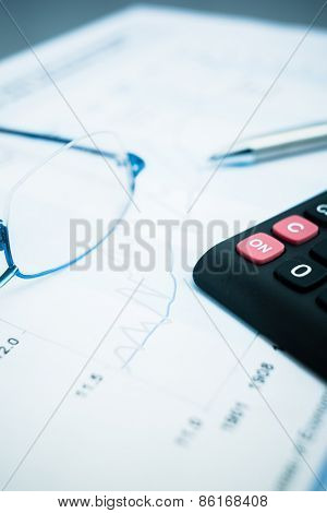 glasses on the finance chart on the desk.