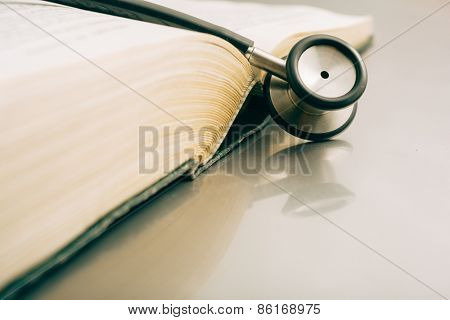 stethoscope and books on white background.