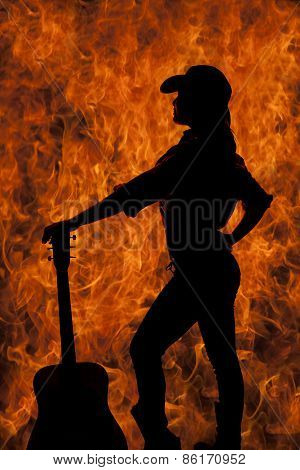 Silhouette Of A Cowgirl With A Guitar Standing By Her