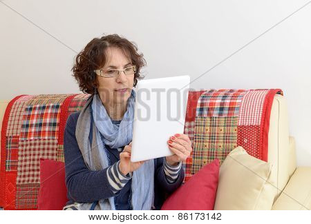 A Middle Aged Woman Looking At A Digital Tablet
