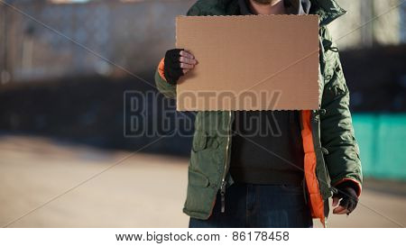 Homeless man holds blank cardboard for you text