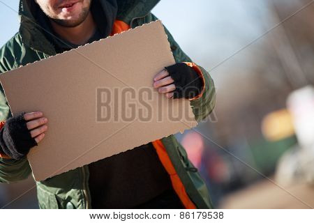 Homeless person with blanck cardboard