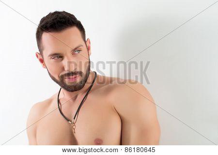 Portrait of smug bearded man posing in studio