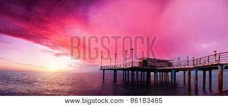 Old metal bridge pier with nobody against beautiful pink dusky sky