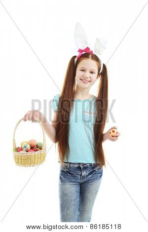 Beautiful little girl wearing Easter bunny ears and holding wicker basket with Easter eggs, isolated on white