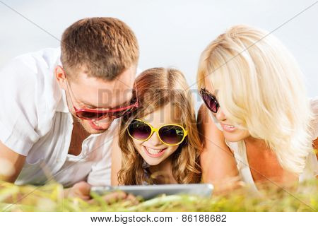 summer holidays, children and people concept - happy family with tablet pc, blue sky and green grass taking picture