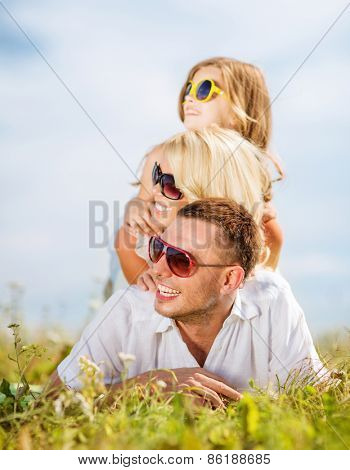 summer holidays, children and people concept - happy family with blue sky and green grass