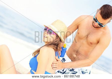 A picture of a man applying sunscreen on the back of his woman at the beach