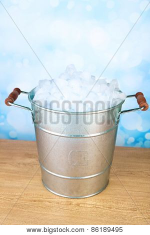 Ice bucket on wooden table on light background