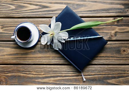 Notebook with cup of coffee and white tulip on wooden background
