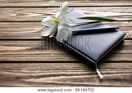 Notebook with pen and white tulip on wooden background