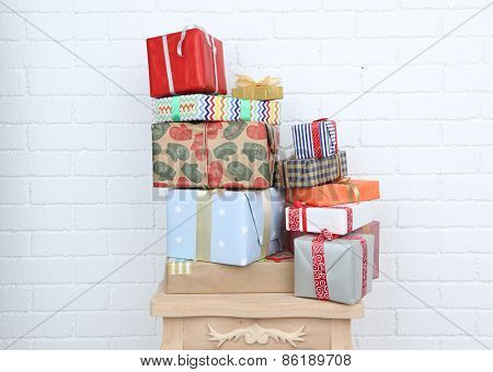 Pile of present boxes on stool on brick wall background