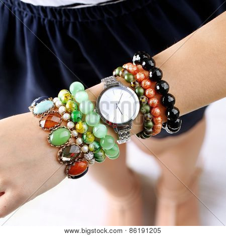 Stylish bracelets and clock on female hand close up