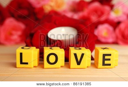 Decorative letters forming word LOVE with flowers and candle on bright background