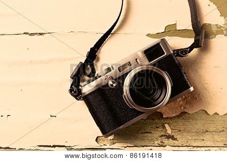 Retro camera on old color wooden table background
