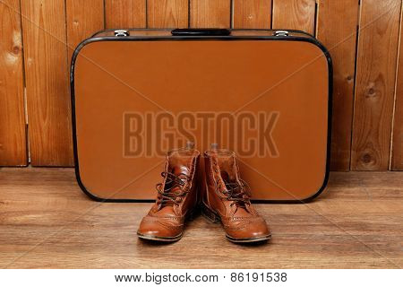 Retro suitcase with male shoes on wooden floor and background