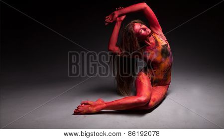 Sport woman in red posing in studio. With body art and face art.
