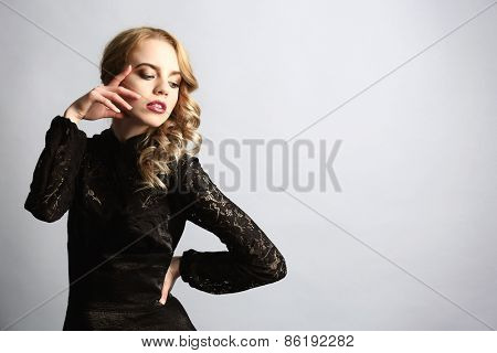 Portrait of beautiful young woman in black dress on light blue background