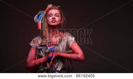Young woman with creative face-art over dark red background.