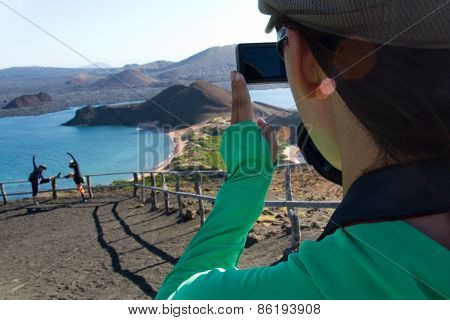 Unidentified woman taking photo of tourists posing in the Galapagos Islands