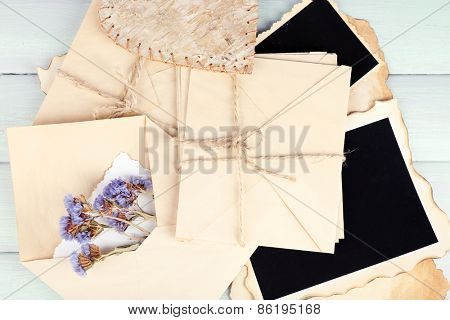 Old envelopes with photo papers and dry flowers on wooden background