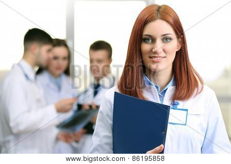 Beautiful young doctor with team in conference room