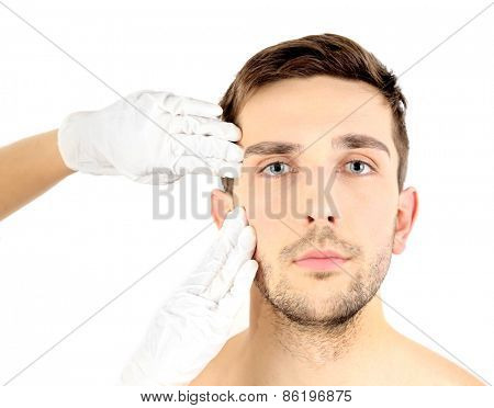 Doctor examines young man isolated on white