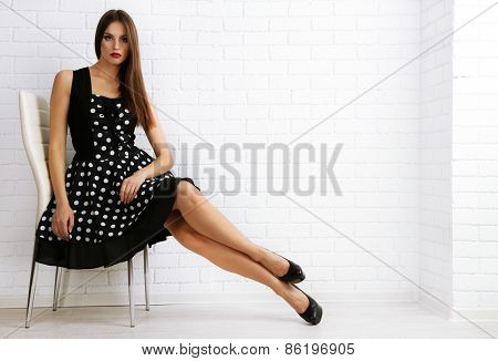 Young woman sitting on chair in dots dress on white brick wall background
