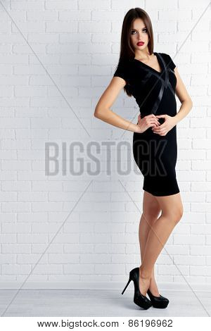 Young woman in black dress on white brick wall background