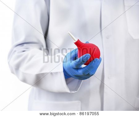 Doctor hand in gloves with medical pink enema syringe isolated on white background