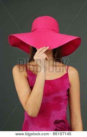 Beautiful young woman in pink dress and hat on dark gray background