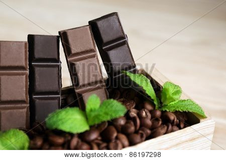 Still life with set of chocolate in wooden box of coffee grains on wooden background