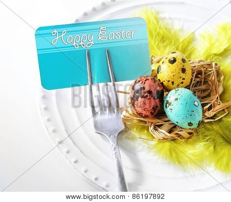 Easter table setting with empty card and Easter eggs, close up