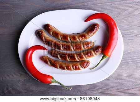 Grilled sausages on plate with chili pepper on table close up