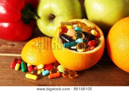 Orange fruit filled colorful pills, on wooden background