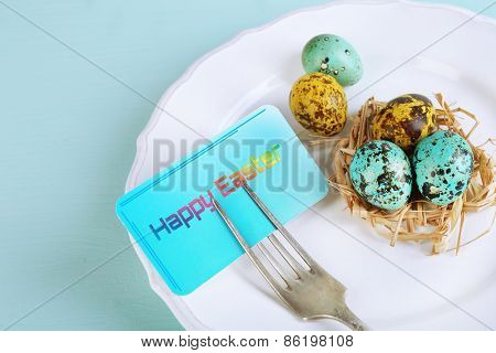 Easter table setting with card and Easter eggs on color wooden background