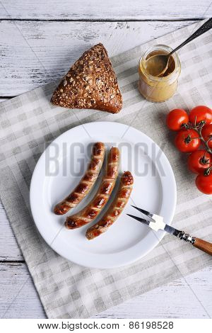 Grilled sausages on plate with bread and cherry tomatoes on table close up