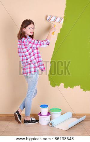 Beautiful woman paints wall in room
