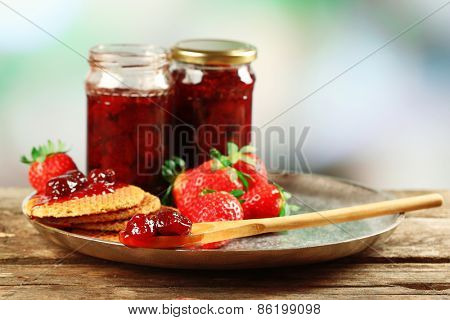 Jars of strawberry jam with berries and wafers on table on bright background